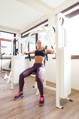 Young Woman Doing Chest Exercise In Fitness Center
