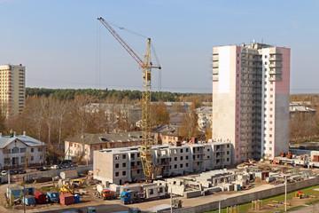 Crane, trucks on construction site and new tall concrete buildin