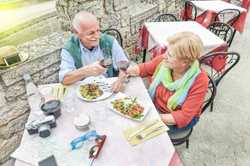 Senior couple toasting wine and eating outdoor