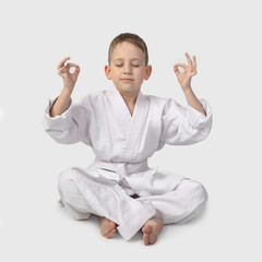 Karate boy meditation with closed eyes on gray background in square