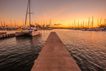 Wooden jetty in Ala Wai Harbor at twilight. Ala Wai Harbor is the largest small-boat and yacht harbor in Hawaii, situated between Waikiki and downtown Honolulu in Oahu Island, Hawaii, United States.