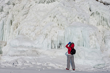 a person in a red jacket taking pictures of the ice flows on the