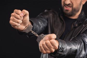 Male criminal getting rid of handcuffs