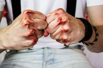 Puños de un hombre joven con sangre en los nudillos