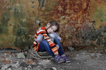 Little girl sits in basement with teddy bear in hands - orphan, homelessness, poverty, despair concept