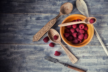 Ripe sweet raspberries in bowl on wooden table. Close up, top vi