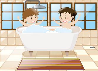 Two boys taking bath together in tub
