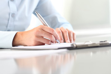 Woman's hands writing on clipboard with a pen; isolated on desk