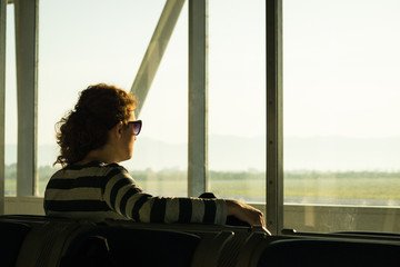 Silhouette of a woman waiting to board a flight in airport