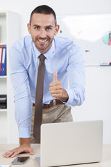Happy businessman working in his office on the laptop