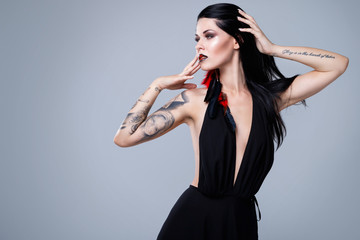 Woman with tattoos wearing black dress