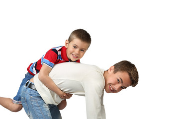 Older boy kneels and carries little brother on back isolated on square white background
