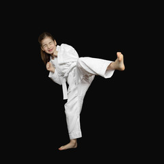Overcoming of fear - little girl in sport white kimono with tight shut eyes beats foot on black background