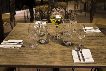 Wine glasses with napkins, glasses and gourmet food, banquet table.