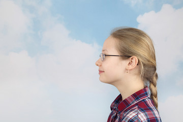 Pretty teenage girl looks ahead on cloudy blue sky background - romantic youth concept