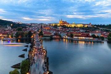 Panorama of Prague with red roofs and Charles bridge from above at dusk, Czech Republic, Europe