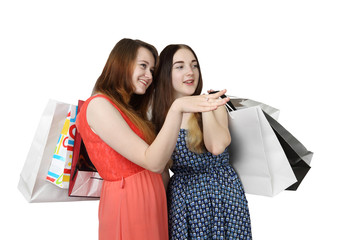 Two pretty girls with shopping bags look to one side isolated on white background