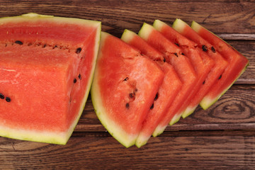 Watermelon quarter and slices on red toned wooden table