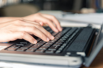 Female hand using keyboard on computer laptop.