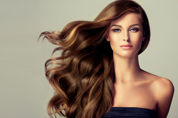 Foto op Textielframe Kapsalon Beautiful model girl with long wavy and shiny hair . Brunette woman with curly hairstyle