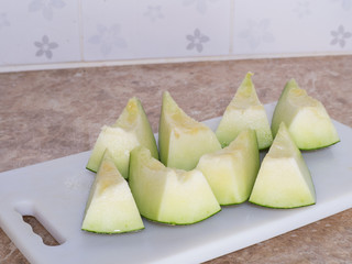 Green japanese melon was cut or divided on a white block in kitc