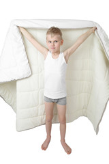 Cute little boy stands going to hide under blanket isolated on white background