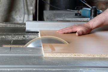Carpenter cuts the board on rotating circular saw blade - Worker hands close up