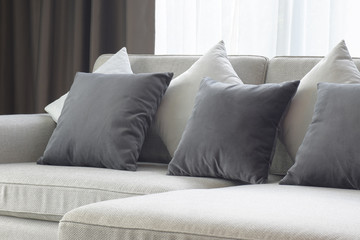 White and gray pillows setting on beige couch in living room