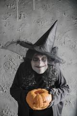 Halloween witch holding a pumpkin