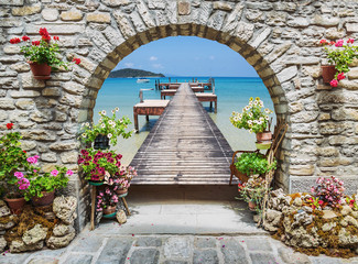 Obraz Seaview through the stone arch with flowers - fototapety do salonu