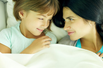Mother and daughter lying together in bed and looking at each other