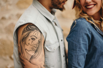 Couple in close up. Man with tattoo of his girlfriend's face