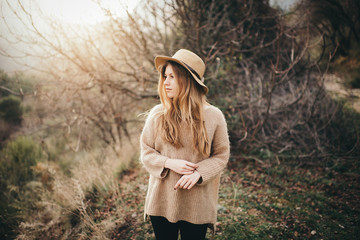 Blonde woman in hat and sweater looking away