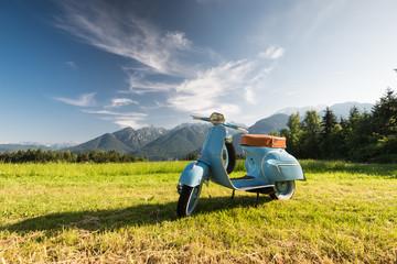 Fotorolgordijn Scooter Blaue Vespa vor Bergkulisse auf Feld