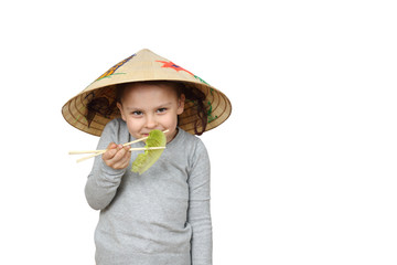 Little Asian girl in Vietnamese hat eats lettuce with chopsticks isolated on white background with copy space for advertising or text message