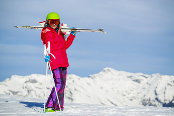 Girl standing with ski on the arms on the fresh powder snow at s