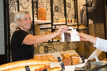 Female shop owner serving sandwich to male customer in bakery