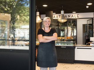 Smiling woman with arms crossed standing in bakery