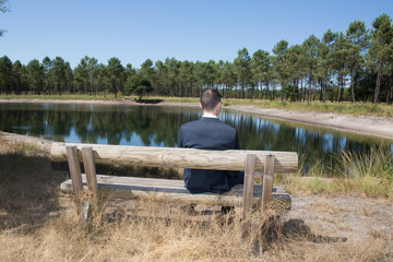 Man sitting alone on park bench, looking down water