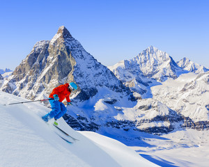 Skier skiing downhill in high mountains in fresh powder snow. Sn