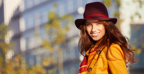 Young beautiful woman in sun autumn street. outdoor city