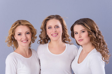Three women dressed in jeans and white t-shirts posing in photostudio on paper grey background