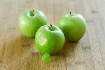 Manzana en mesa de madera con un corazon (concepto de dieta y salud)