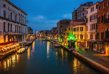 VENICE, ITALY - AUGUST 21, 2016: Famous architectural monuments, ancient streets and facades of old medieval buildings at night time close-up on August 21, 2016 in Venice, Italy.