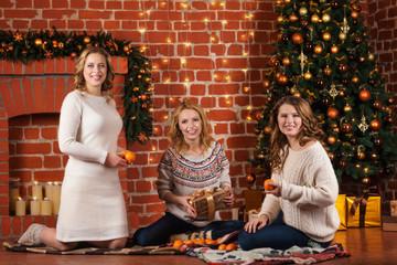 three pretty women open gifts near christmas tree