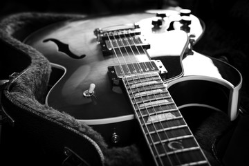 Acoustic guitar close up in dark background.B/W image.