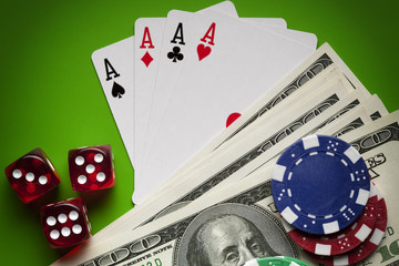 Playing cards, poker chips, dices and money on green table