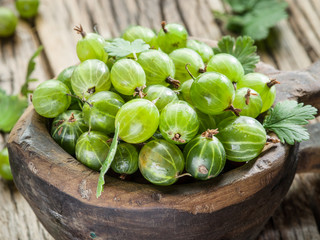 Gooseberries in the wooden bowl on the table.