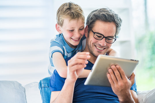 a father and his young son having fun by  playing on a tablet