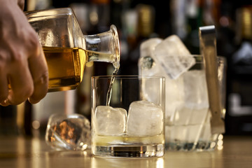 Barman is serving a good whiskey on the rocks